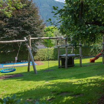 Spielplatz mit Trampolin, Rutsche, Kletterwand, Schaukel und Sandkasten